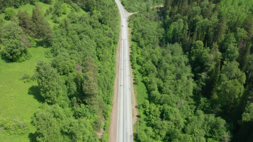 Flight over a forest area overlooking an asphalt road. The road has an exit from the main road. Cars are driving along the road. Sunny day. #1040050799