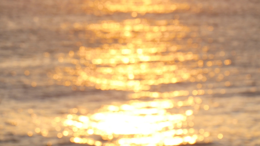Golden glisten of sunlight reflects on the sunset sea surface. Sparkling sunlight over the calm water.  | Shutterstock HD Video #1040068349