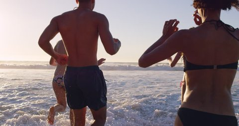 Group of friends swimming in the sea at sunset running into water getting wet and making splashes RED DRAGON