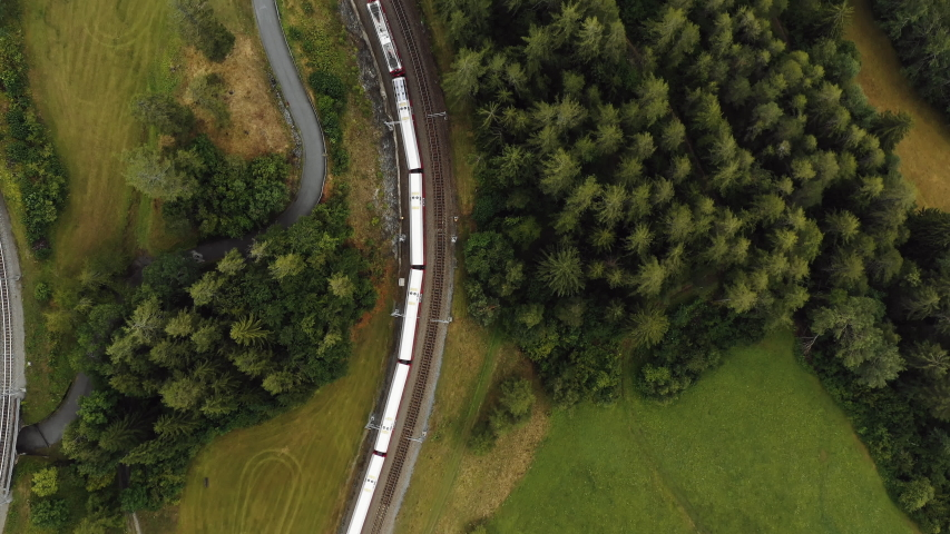 Top view, drone tracking epic red Glacier Express train cruising along peaceful summer Swiss Alps countryside villages. | Shutterstock HD Video #1040223029
