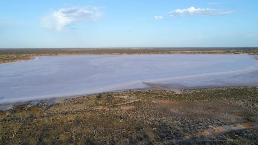 Aerial pan across pink salt lake in Australian desert in the morning | Shutterstock HD Video #1040389919
