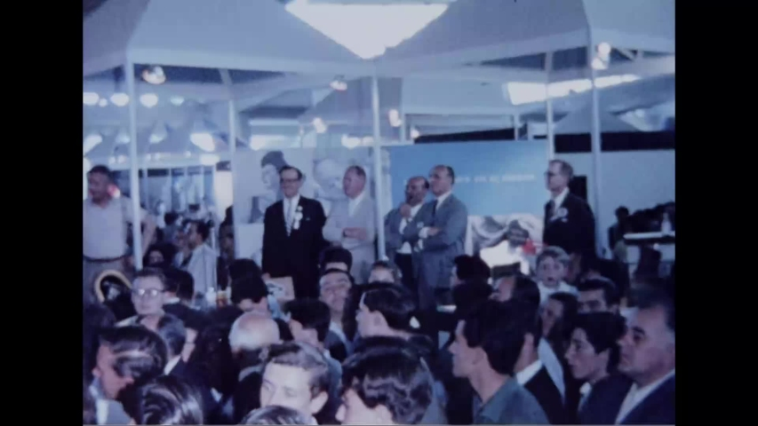 CIRCA 1964 - Huge crowds swarm an exhibit at the New York's World Fair.