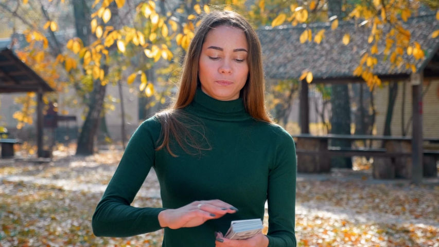 Young attractive brunette woman throwing a lot of money in the air in park. Girl enjoys of cash. Huge wealth of money. Employee salary. Cash money payment. Successful business concept. 4K footage | Shutterstock HD Video #1040532149