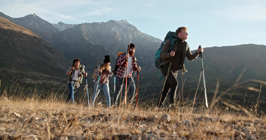 Group of four hipster friends travelling together, hiking and adventuring in mountains. Students on vacation - friendship, travel destination concept 4k footage | Shutterstock HD Video #1040696399