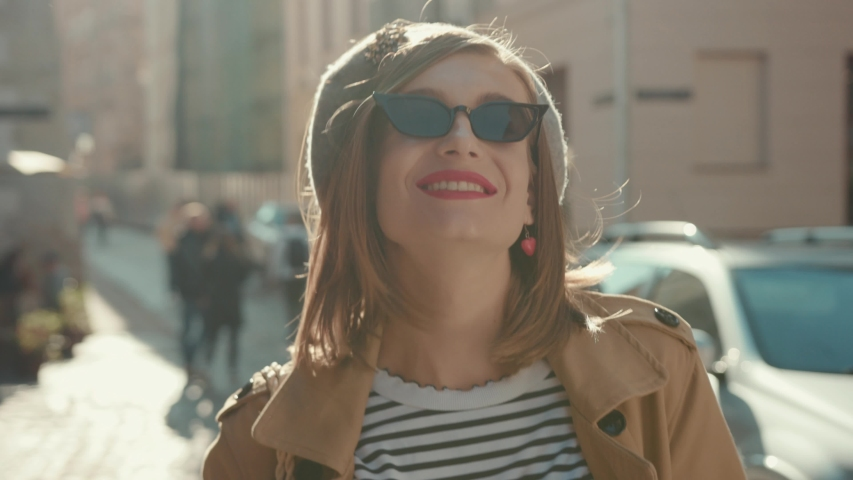 Portrait young attractive smile woman look at camera poses smile air kiss at city center feel happy fashion girl face technology sun beautiful slow motion street   Shutterstock HD Video #1040737919