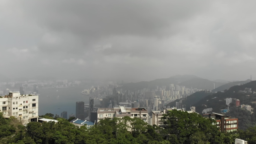 Aerial view from Victoria Peak to Hong Kong. A large number of skyscrapers, Vitoria Bay. Cloudy weather, smog   Shutterstock HD Video #1040818949