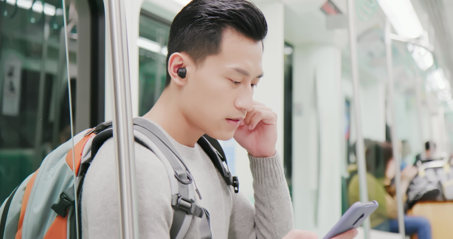 Asian man use wireless earbuds to listen music or watch video on the metro | Shutterstock HD Video #1040827259