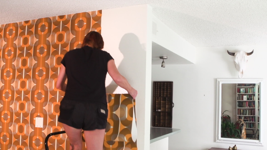 Real woman improving, renovating and decorating her home by hanging 1970's retro wallpaper | Shutterstock HD Video #1040883209