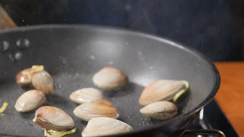 Closeup shot of chef hands cooking mussels in shells tossing, mixing and throwing on pan., seafood being cooked in frying pan at restaurant kitchen, Pasta with seafood. Slow motion. Shot in hd | Shutterstock HD Video #1040891369