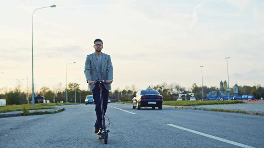 Modern man riding on green transport electric powered scooter on road in open space landscape at sunset. Ecological trasportation. #1040891759