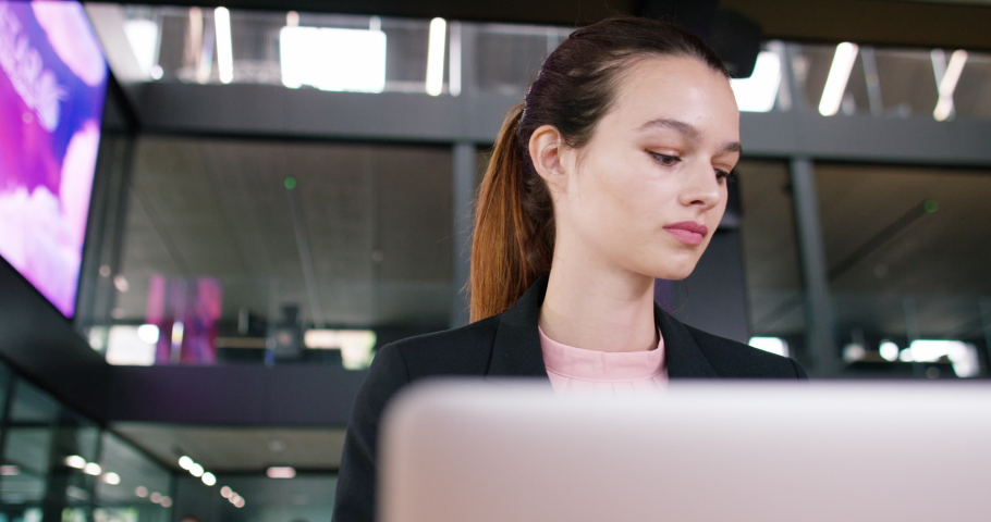 4K Young businesswoman working on laptop in modern office with large electronic screen displaying data. Slow motion. | Shutterstock HD Video #1040893079