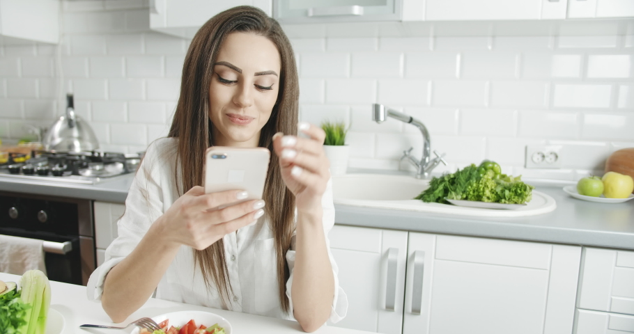 Attractive young brunette female communicating via social network and feeling happy, plate of salad on kitchen table | Shutterstock HD Video #1040894159