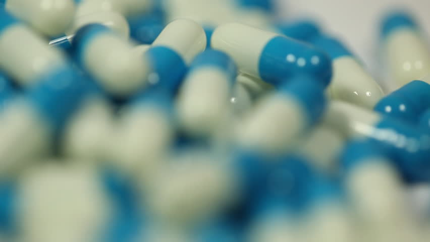 Pills rotate slowly in macro. Nice medical background
