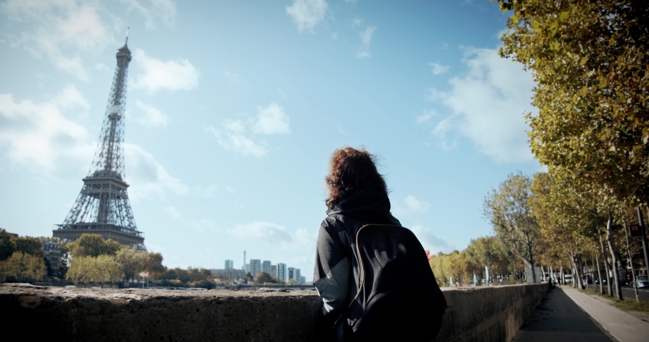 Tourist Girl with a backpack looks at the tower and starts walking the city of Paris, past the Eiffel Tower and the Seine River, and views the city, wide shot | Shutterstock HD Video #1040971829