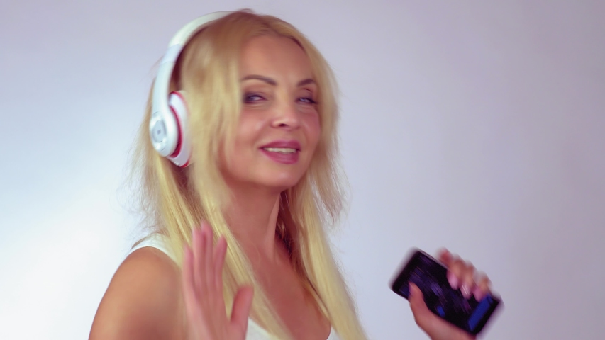 Mature happy beautiful woman enjoying listening music with headphones dancing on a light background | Shutterstock HD Video #1040980259