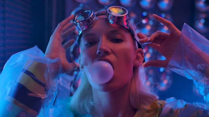 Portrait of Young Sexy Playful Blond Girl Standing in Clubbing Dressed Wear in Pink Blue Rays Light and Chewing Candy. Lady Blowing Bubble Gum. 20s Woman Looking at Camera Closeup. 4k Slow Motion