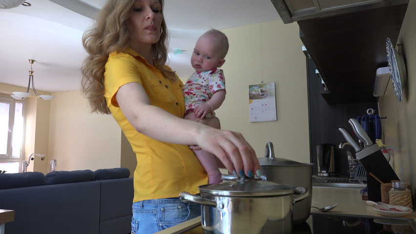 Pretty woman in yellow holding baby girl in arms, mix spaghetti meal in kitchen. Woman prepare food in steamy pot. Static shot. 4K UHD video clip.