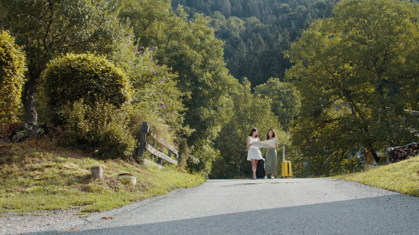 Travellers with suitcases using map in Alpine village | Shutterstock HD Video #1041082609