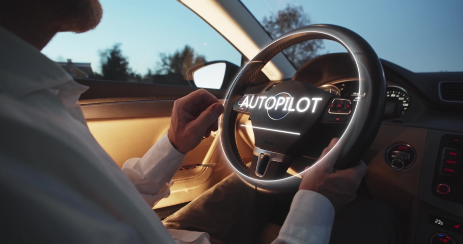 A man driving futuristic car activates autopilot on augmented reality hologram hud. Vehicle starts autonomous self-driving. Hands free system. Concept of Driverless Future Technology in transport. | Shutterstock HD Video #1041133339
