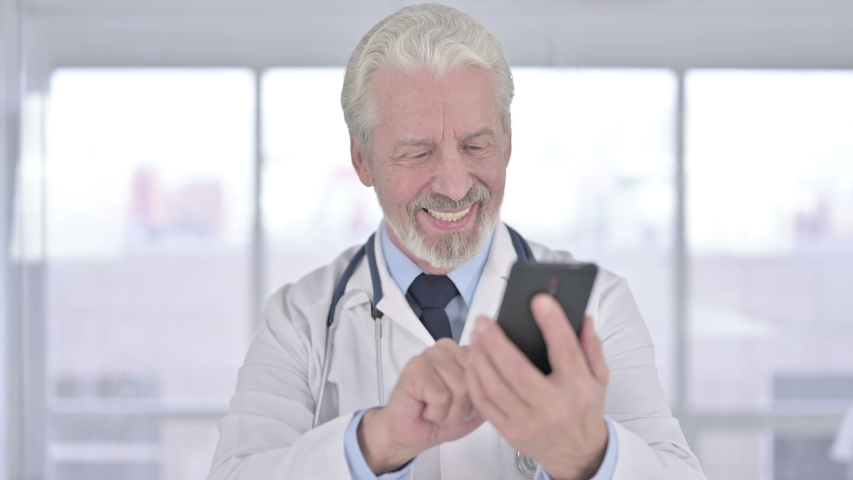 Portrait of Cheerful Senior Old Doctor using Smartphone in Office | Shutterstock HD Video #1041140749