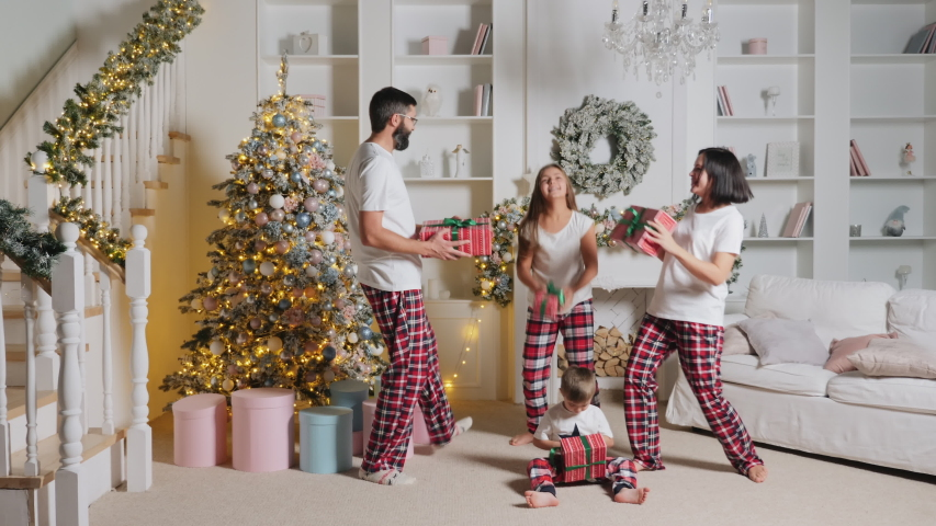 A cheerful European family of four in pajamas is dancing funny with presents in the living room of their home, decorated for Christmas, near the Christmas tree and stairs. A little boy sits on the | Shutterstock HD Video #1041142669
