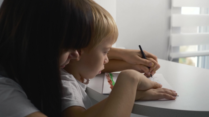 Happy family. Mom and son paint a picture in the album. Home schooling. Doing homework. Teamwork | Shutterstock HD Video #1041222049