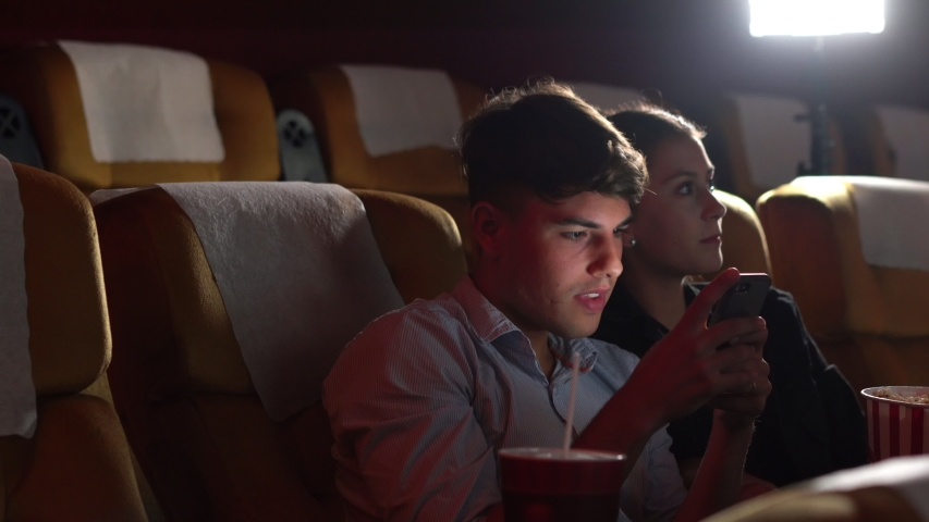 Men playing games on mobile phones he makes his girlfriend annoy and Interfere with watching the movie. | Shutterstock HD Video #1041306289