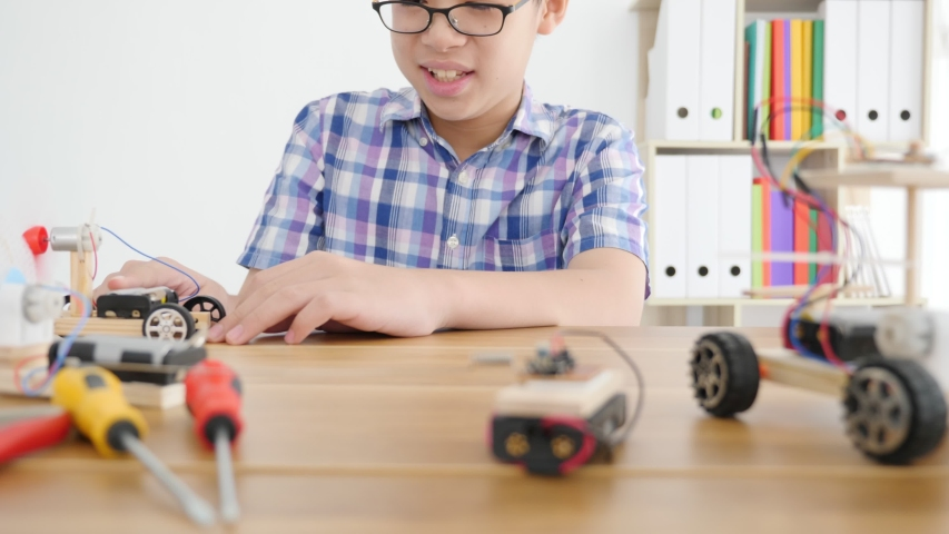 Young Asian boy creating a toy car that is powered by wind from propellers.   | Shutterstock HD Video #1041312139