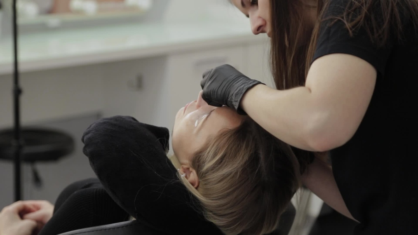 Professional beautician in a beauty salon paints eyelashes to a client. | Shutterstock HD Video #1041421039