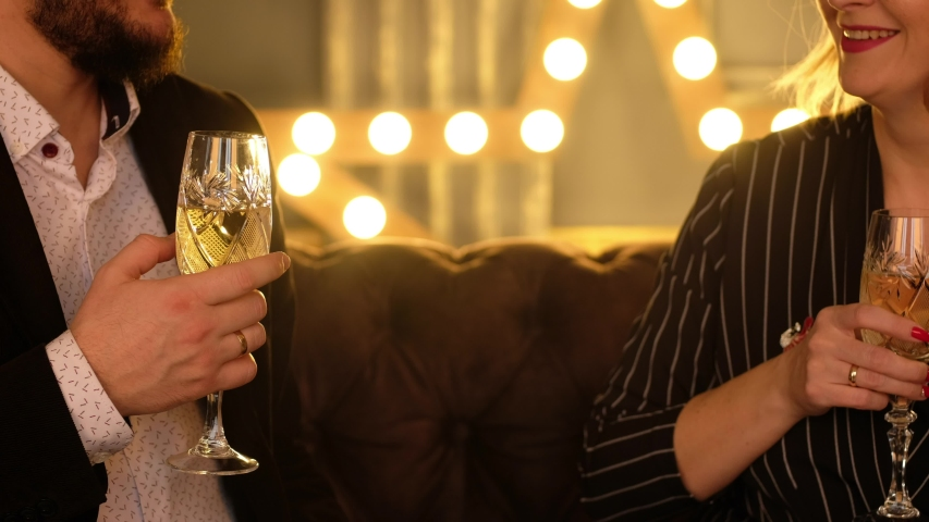 A man and a woman drink festive sparkling wine in beautiful glasses. Lovers celebrate Christmas and clink champagne. | Shutterstock HD Video #1041456919