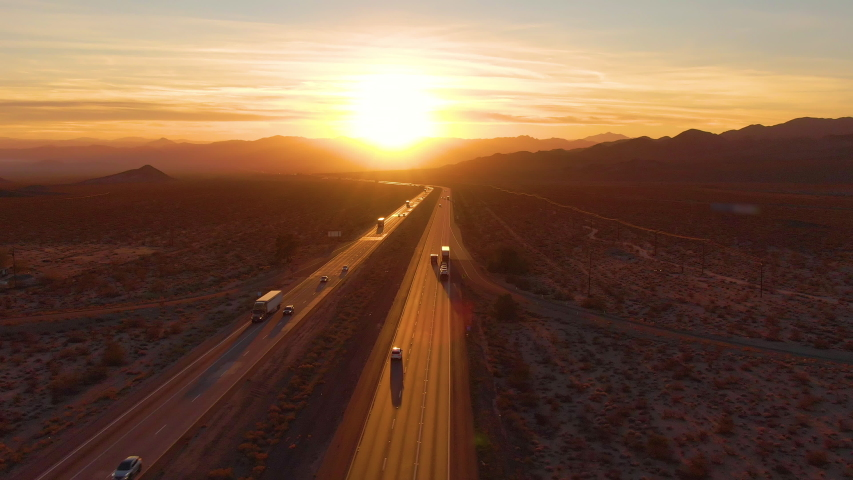 AERIAL, LENS FLARE: Scenic shot of 18 wheeler trucks and cars crossing Mojave desert at dusk. Golden evening sun rays shine on the traffic moving up and down the straight freeway in rural California. | Shutterstock HD Video #1042216279