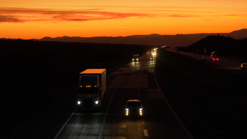 DRONE: Scenic shot of evening traffic driving along the highway leading across the Mojave desert at twilight. Commuters and truck drivers cross the Mojave desert on a picturesque summer evening. | Shutterstock HD Video #1042216339