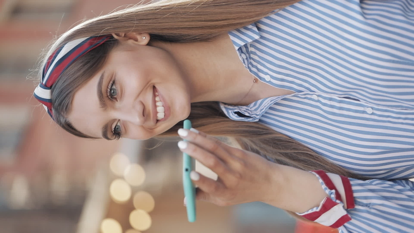 Vertical Video. Young Attractive Caucasian Girl with Brown Hair and Fashionable Headband Wearing in Striped Shirt Using her Smartphone Voice Message and Scrolling Standing at the City Street   Shutterstock HD Video #1042267249
