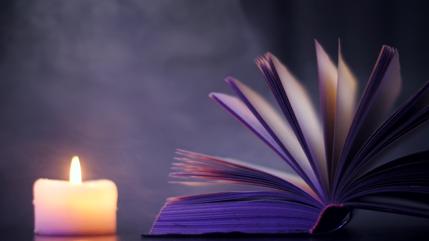 Near the open book, a candle burns and colored, magical smoke flies.   Shutterstock HD Video #1042340389