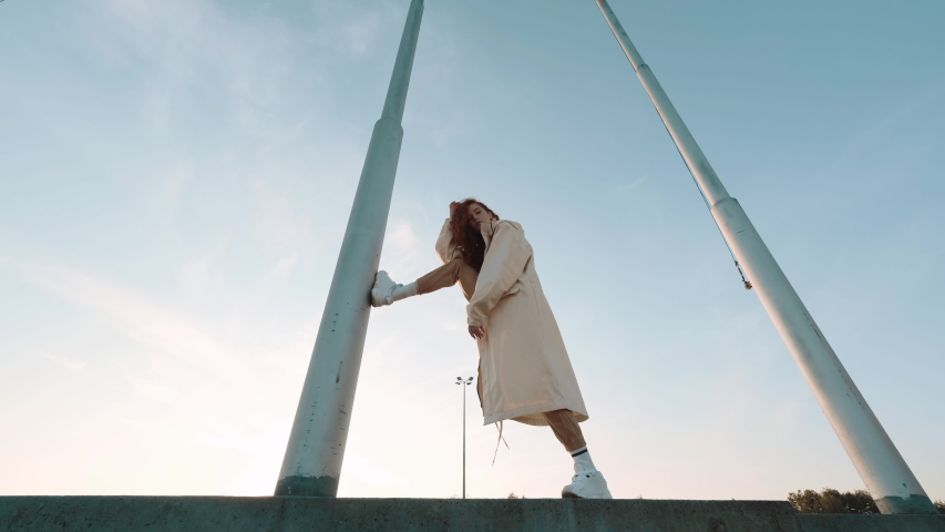 Young Contented Girl. Urban Fashion Concept. Pretty Girl With Long Hair. She Holds One Foot On Vertical Electric Pole. | Shutterstock HD Video #1042425169