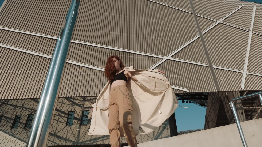 Young Red-Haired Girl On The Street. Girl Has Long Curly Hair. Urban Fashion Concept. Pretty Girl In Cloak And Sneakers Posing Near Modern Building. | Shutterstock HD Video #1042425229