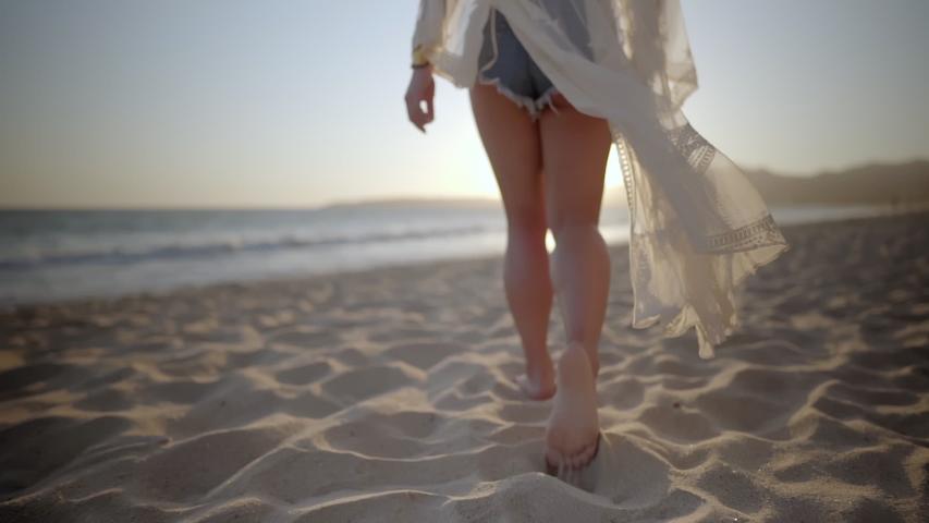 Woman walks along beach barefoot wearing light flowing dress blowing in the wind | Shutterstock HD Video #1042455829