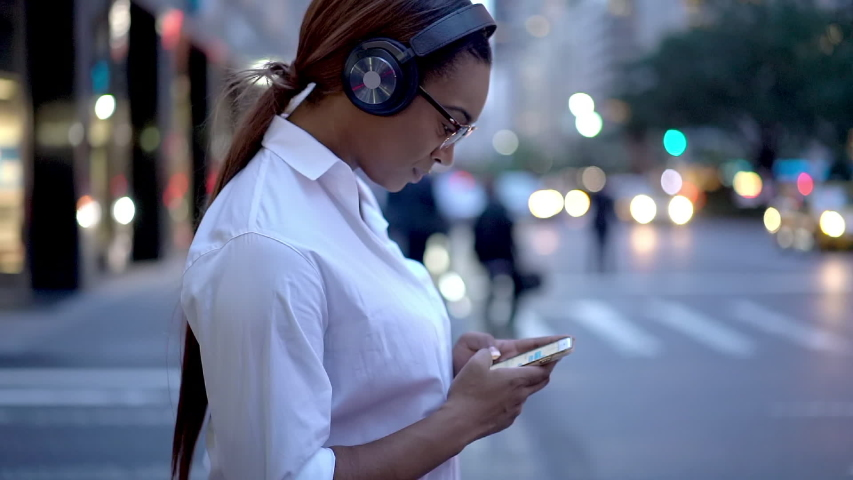 African American manager in electronic earphones waiting for crosswalk in downtown, slow motion of female trainee getting to office for internship day using cellphone device for communicate outdoors  | Shutterstock HD Video #1042487839