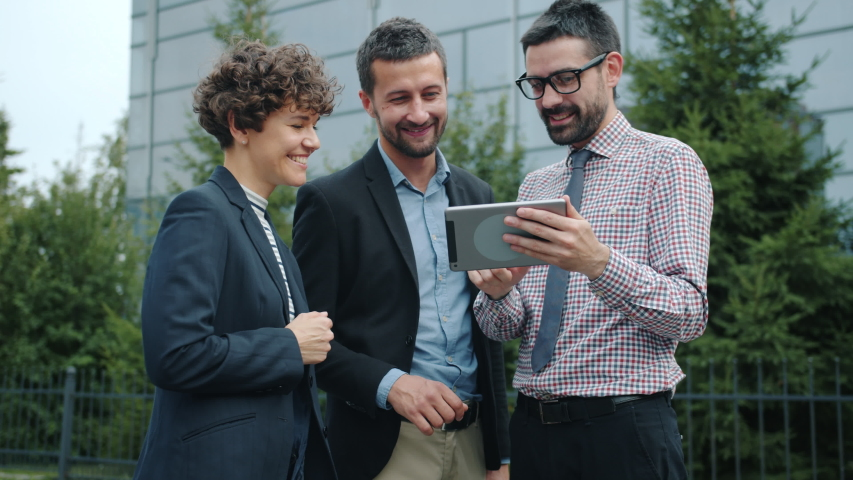 Slow motion of happy young colleagues guys and girl standing outdoors discussing work holding tablet portable computer. People and communication concept. | Shutterstock HD Video #1042493149
