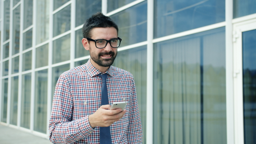 Cheerful office worker is texting using smartphone smiling walking outdoors in city street near glass wall office building. People and communication concept. | Shutterstock HD Video #1042506649