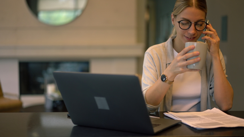 Smart casual freelancer in classic glasses communicating with colleague during paper accounting and laptop remote working, Caucasian woman using cellphone for contact phoning indoors  | Shutterstock HD Video #1042552159