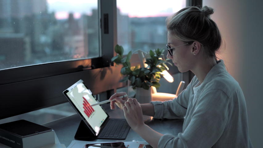 Young female freelancer calling to remote colleague for discussing web accounting on touch pad, skilled woman drawing statistic charts on digital tablet while communicating via smartphone device  | Shutterstock HD Video #1042555969