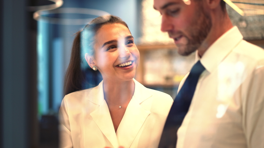 Caucasian colleagues enjoying collaboration during working process in office interior, happy man and woman smiling while communicating about startup business project | Shutterstock HD Video #1042559779