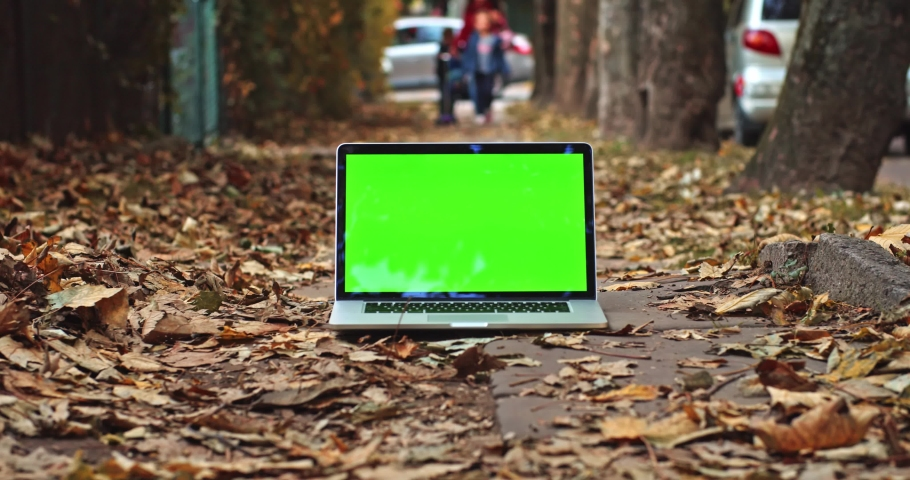 Green screen laptop with romantic fiery autumn city and walking children on background. Free mock up content. Chroma-key notebook display. Freelance business app. Social networking. Online shopping. | Shutterstock HD Video #1042594459