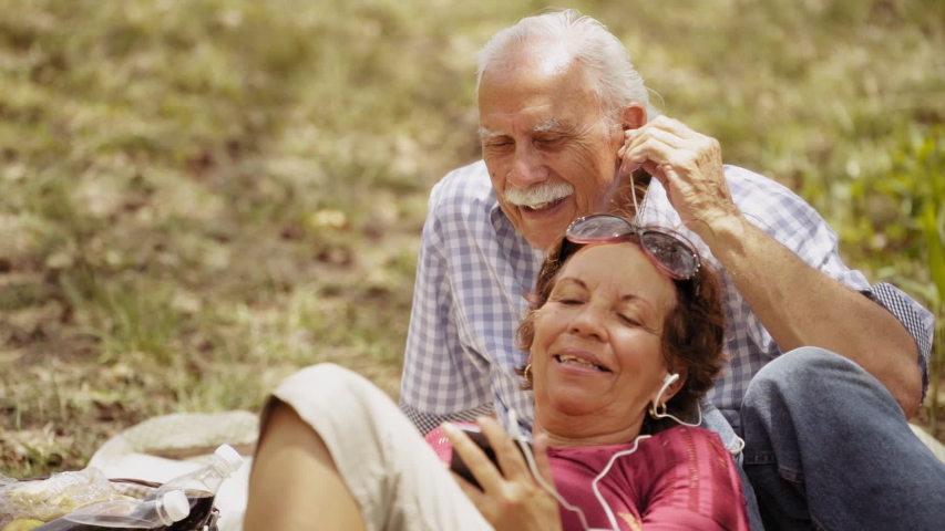 Old people, senior couple, elderly man and woman, husband and wife in park, retired seniors. Outdoors activity, leisure, fun, recreation. Grandpa and grandma listening to song, music with mp3 player  | Shutterstock HD Video #1042616869