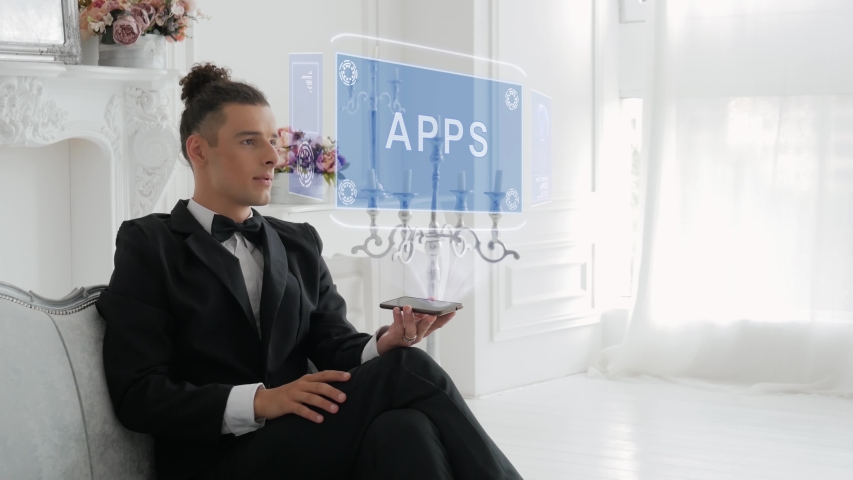 Guy businessman activates conceptual HUD hologram on smartphone with text APPS. Young man in a white shirt and a jacket with a holographic screen on a background of the luxury room | Shutterstock HD Video #1042689259