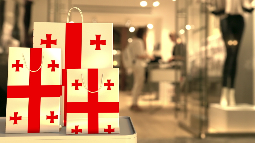 Flag of Georgia on the paper shopping bags against blurred store entrance. Retail related clip | Shutterstock HD Video #1042690459