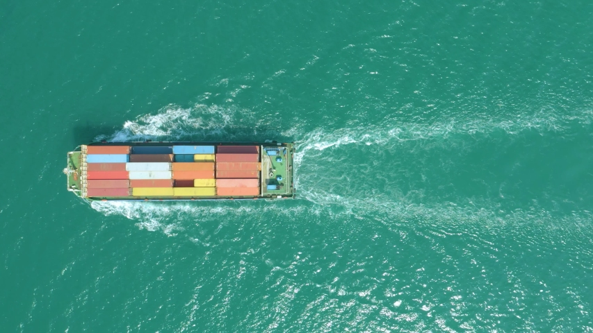 Top down Aerial View of a large container ship sailing at the sea for transporting shipments to other countries   | Shutterstock HD Video #1042702669