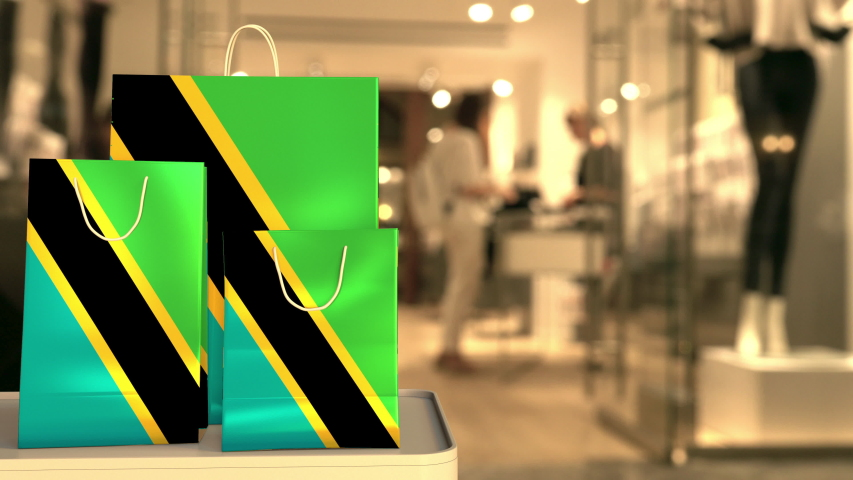 Flag of Tanzania on the paper shopping bags against blurred store entrance. Retail related clip | Shutterstock HD Video #1042715509