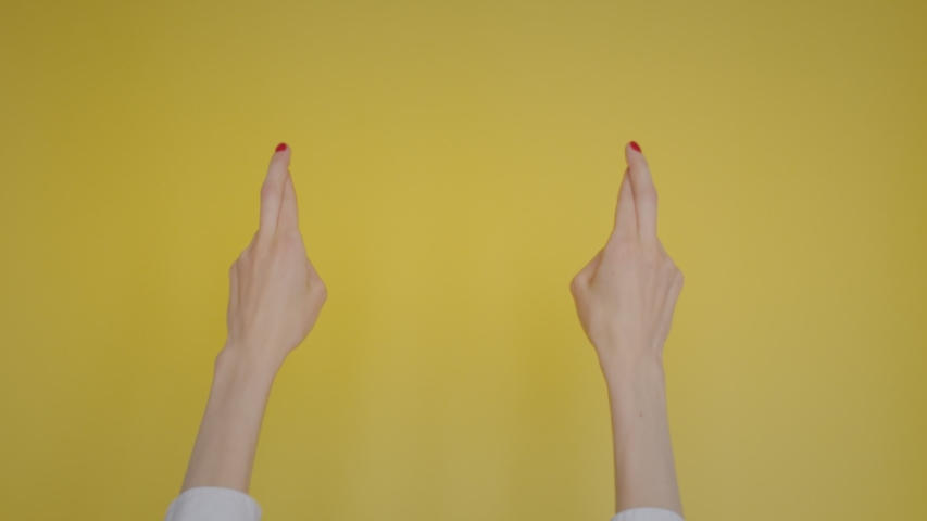 Woman hands keeping fingers crossed, making wish isolated over pastel yellow background in studio. Copy space for advertisement. With place text or image promotional content. | Shutterstock HD Video #1042723609